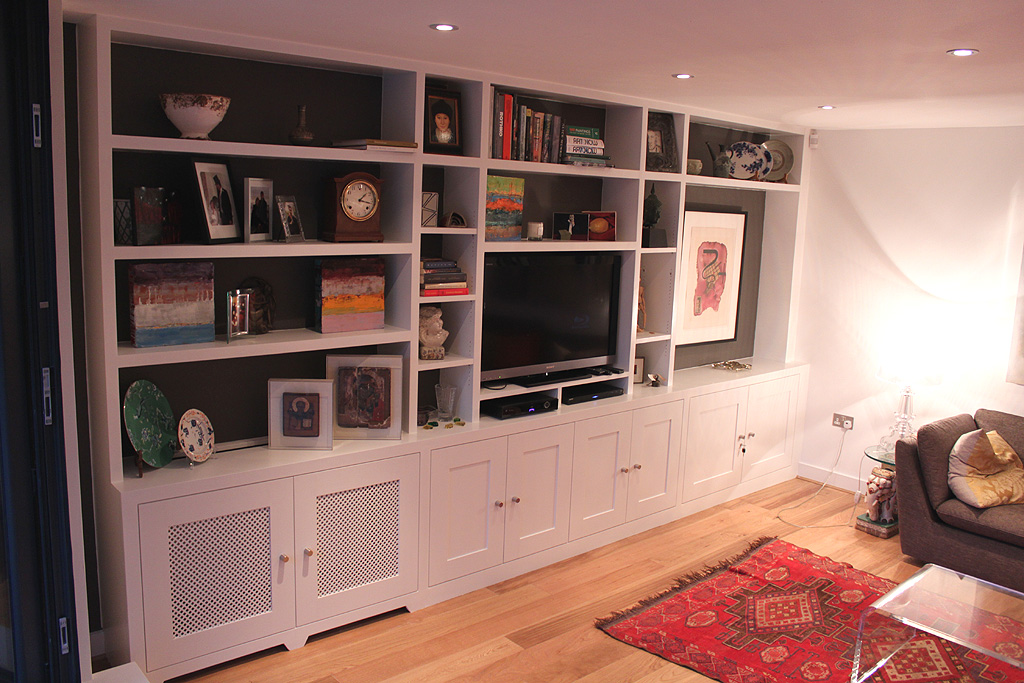 Fitted bookcase around tv and radiator in Chiswick