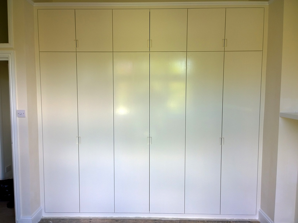 Plain doors fitted wardrobe with cut out handles
