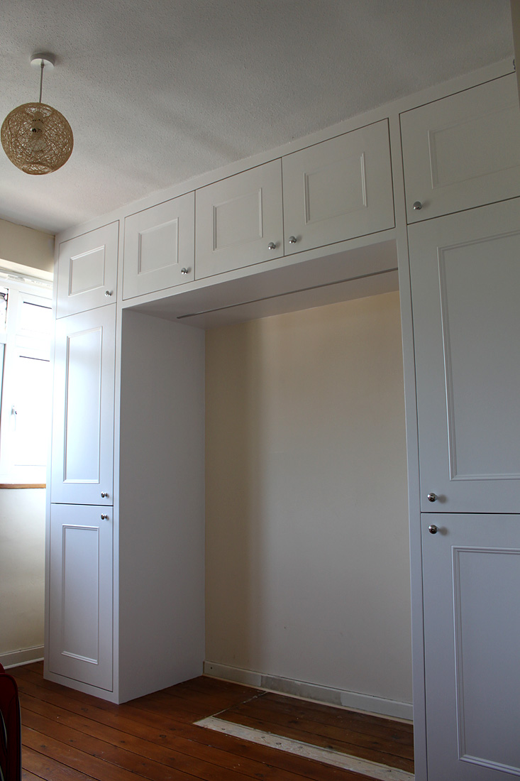 Shaker wardrobe with cupboards above the bed and LED light