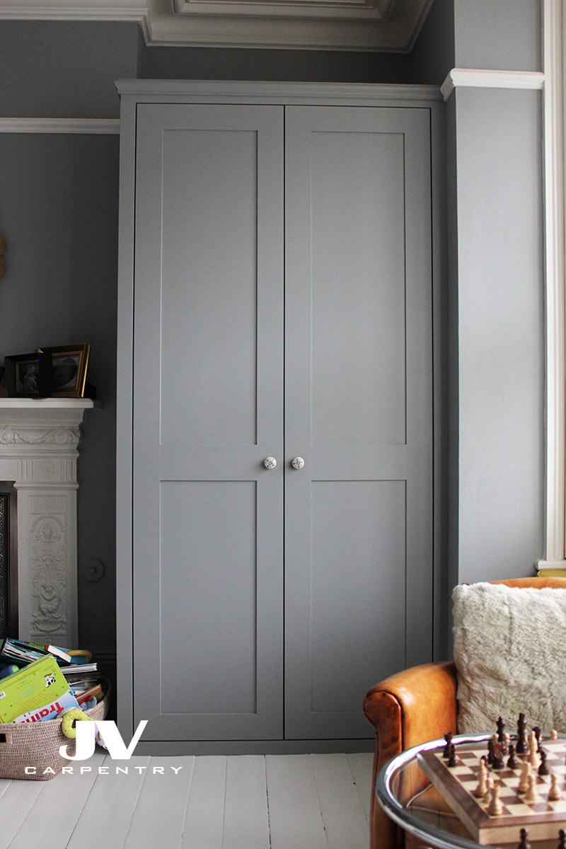 Grey alcove fitted wardrobe made with the same picture raila over the top and two shaker doors. This wardrobe made with drawers, hanging rail and shelves inside