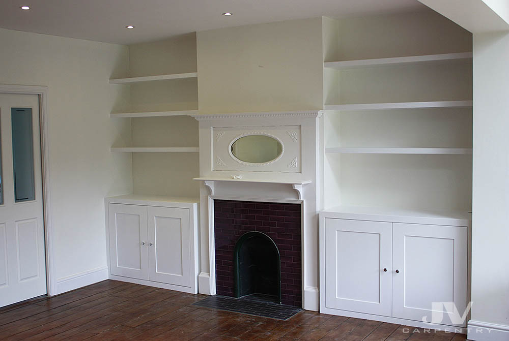A pair of bespoke alcove cabinets with floating shelves