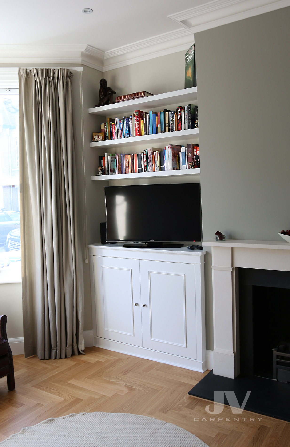 alcove fitted cabinet with tv and shelves above