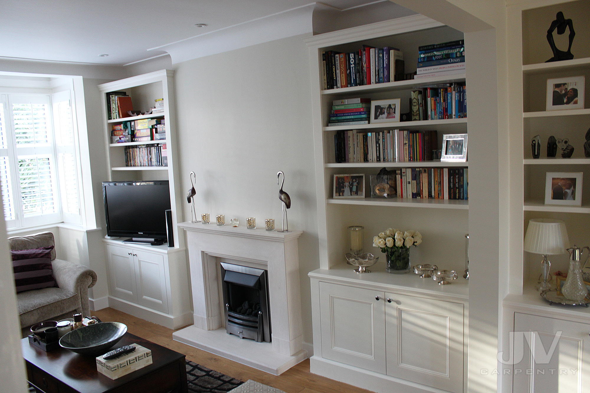 Living room alcoves shelving either side of the nice fireplace
