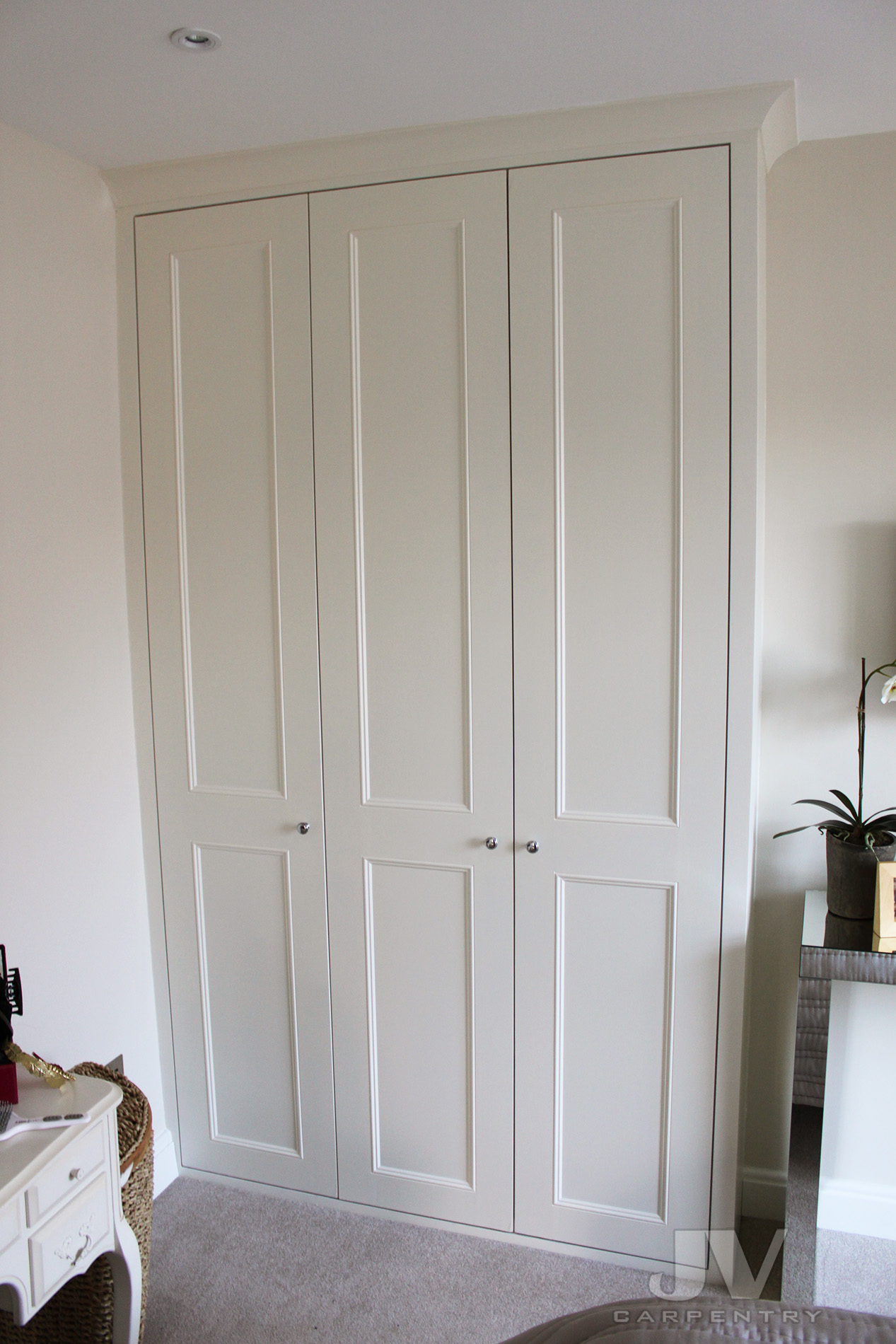 built in wardrobe with tree doors from floor to the ceiling.