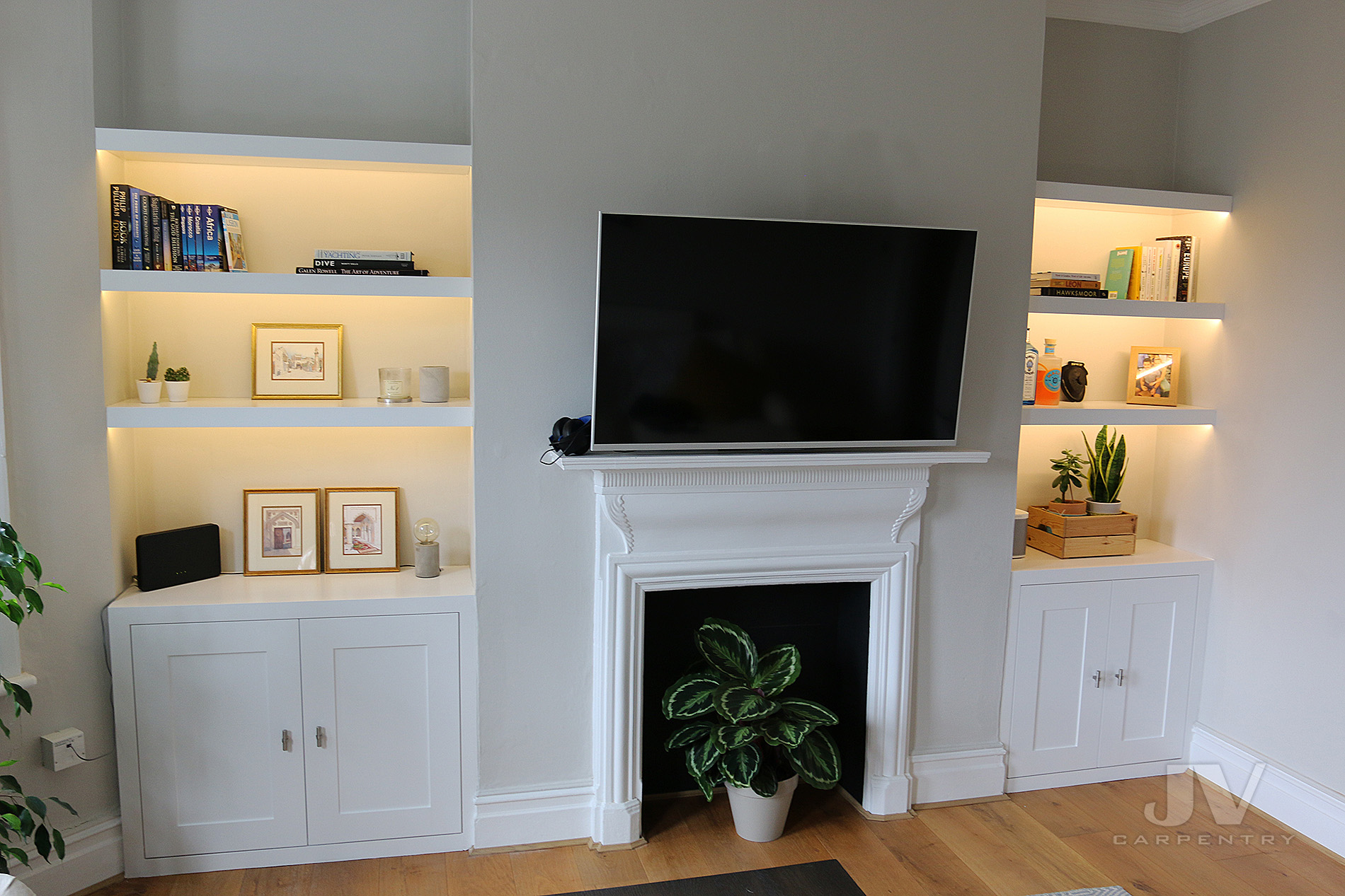 alcove bookshelves with light and cabinet either side of the chimney breast