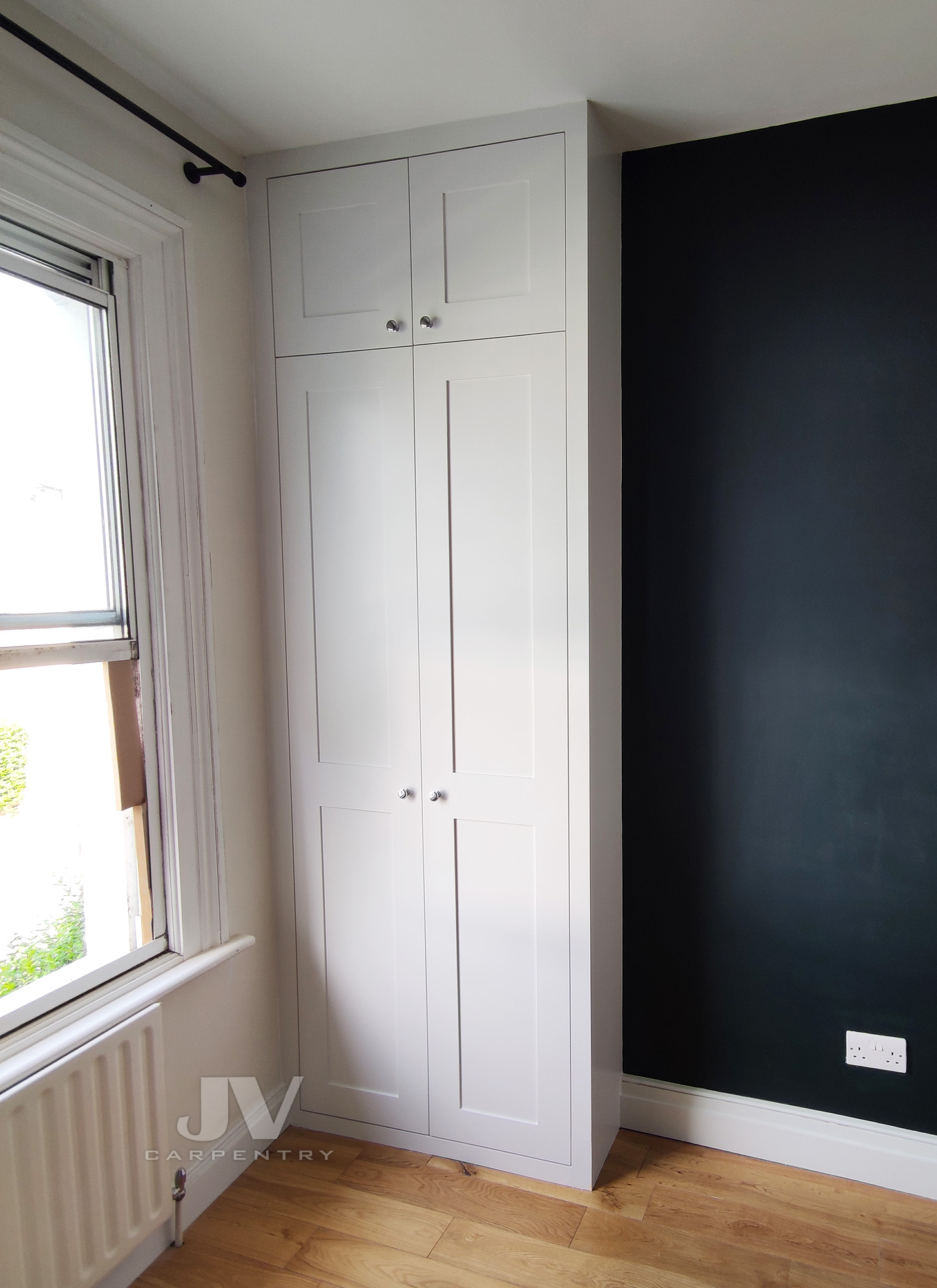 fitted wardrobe in an alcove by the window