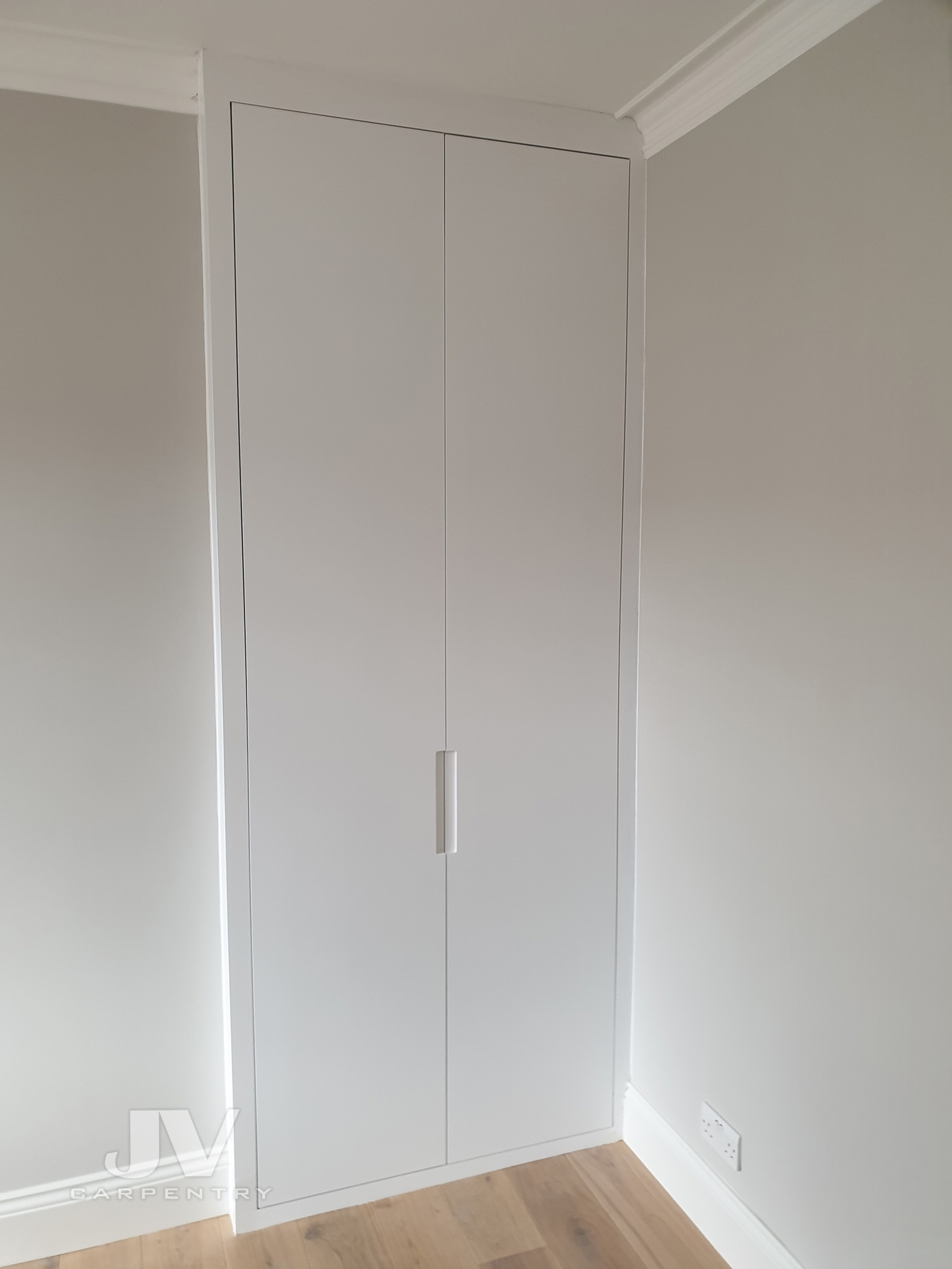 Fitted alcove wardrobe with plain doors