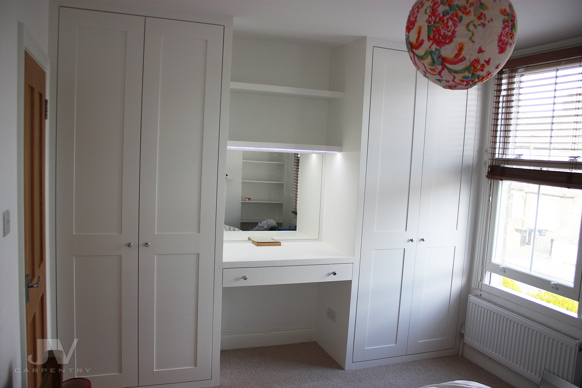 Dressing table fitted between two wardrobes