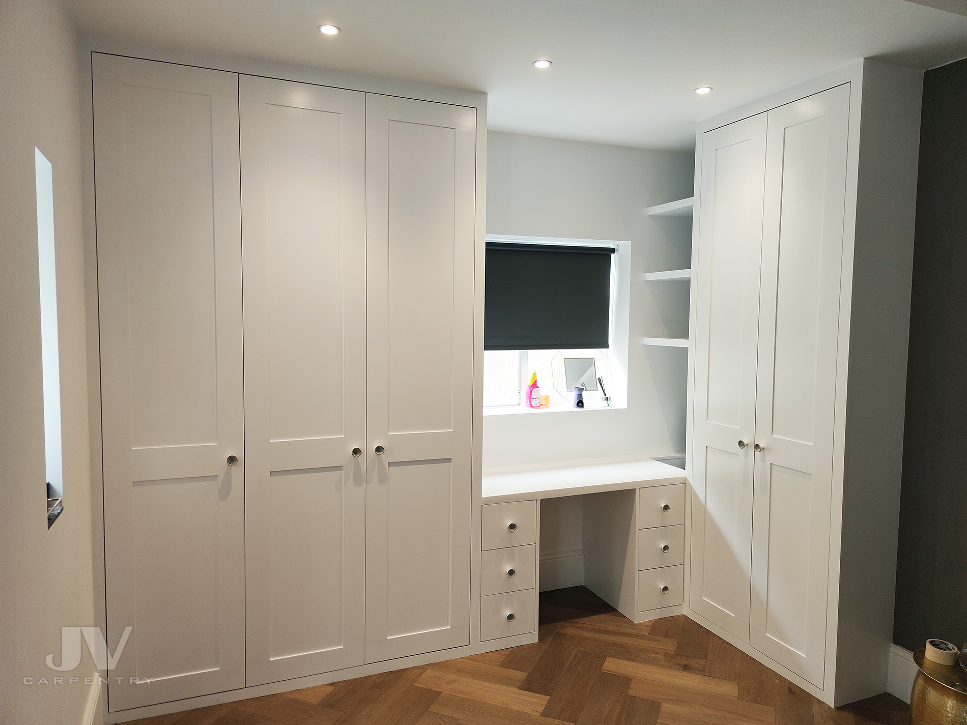 Fitted wardrobe built around window with dressing table