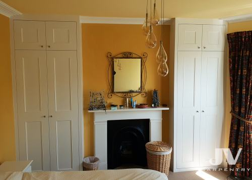 Hand crafted alcove wardrobes either side of the chimney