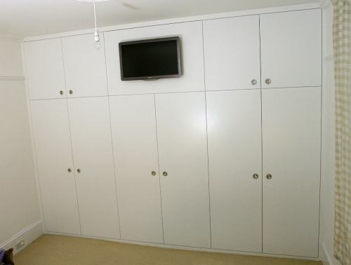 Fitted wardrobe with flush handles and TV