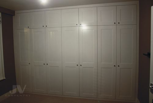 Built in wardrobe across hole bedroom wall