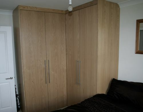 L shaped oak veneer fitted wardrobe