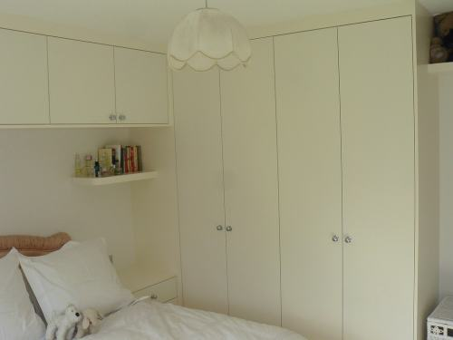 plain wardrobe with shelves and cupboards above the bed