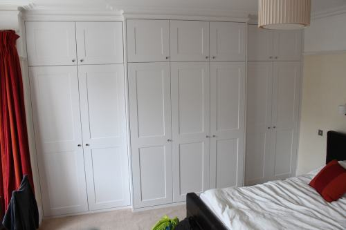 A full wall length bespoke wardrobe fitted around chimney breast